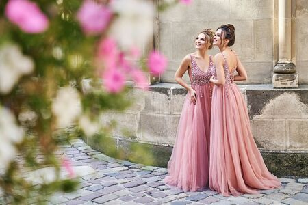 Beautiful bridesmaids in gorgeous elegant stylish red pink violet floor length v neck chiffon gown dress decorated with sequins sparkles and rhinestones holding flowers bouquets. Wedding day in old beautiful European city. Copy space.