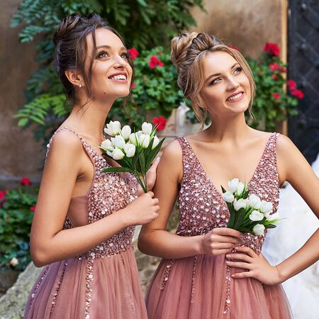 Beautiful bridesmaids in gorgeous elegant stylish red pink violet floor length v neck chiffon gown dress decorated with sequins sparkles and rhinestones holding flowers bouquets. Wedding day in old beautiful European city. Foto de archivo
