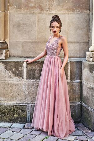 Beautiful bridesmaid lady in gorgeous elegant stylish red pink violet floor length v neck chiffon gown dress decorated with sequins sparkles and rhinestones holding flowers bouquets. Wedding day in old beautiful European city.
