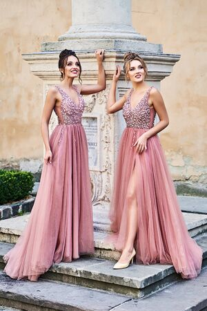 Beautiful bridesmaids in gorgeous elegant stylish red pink violet floor length v neck chiffon gown dress decorated with sequins sparkles and rhinestones standing by an old column. Wedding day in old beautiful European city. Copy space.