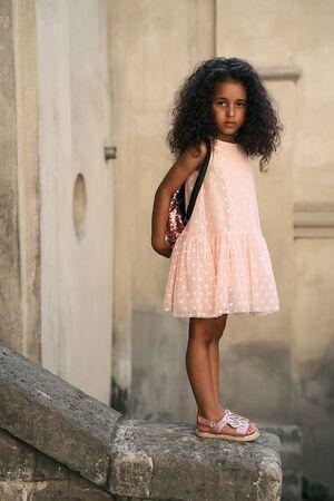 Adorable petite fille métisse de 4 ans avec de beaux cheveux noirs bouclés épais portant une robe rose, des sandales et un sac à dos debout sur un bord de pierre dans la rue de la vieille ville.