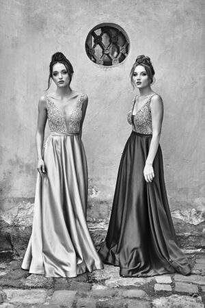 Two beautiful bridesmaids girls blonde and brunette ladies wearing elegant full length satin folded bridesmaid dress with silver sequined camisole top with sequins. European old town location for wedding day. Black and white.