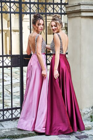 Two beautiful bridesmaids girls blonde and brunette ladies wearing elegant full length purple violet lilac lavender satin folded bridesmaid dress with silver sequined camisole top with sequins. European old town location for wedding day.