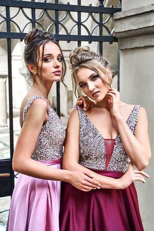 Zwei schöne Brautjungfern Mädchen blonde und brünette Damen tragen elegantes in voller Länge lila violett lila Lavendel Satin gefaltetes Brautjungfernkleid mit silbernem Pailletten-Kamisole-Top mit Pailletten. Europäische Altstadtlage für Hochzeitstag. Standard-Bild