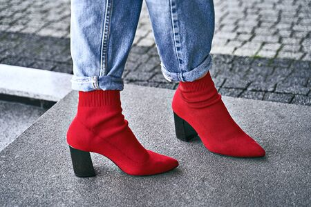 Woman legs in red sexy trendy stretch knitted fabric pointed toe block heel sock boots shoes and blue denim jeans pants