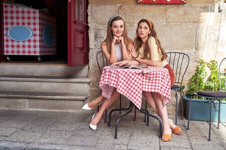 Young beautiful girls dressed in retro vintage style enjoying the old european city lifestyle in street cafe Stok Fotoğraf