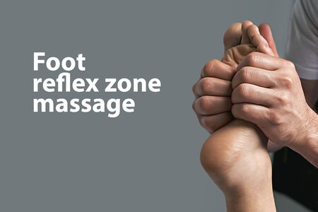 Male masseur doing massage on female foot reflex zone in the spa salon. Copy space with sample text on light grey background.
