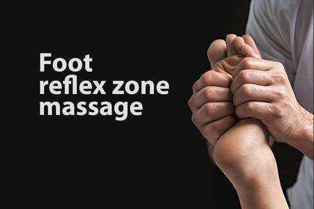 Male masseur doing massage on female foot reflex zone in the spa salon. Copy space with sample text on black background.