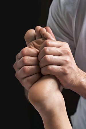 Male masseur doing massage on female foot reflex zone in the spa salon.