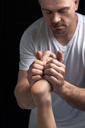 Male masseur doing massage on female foot reflex zone in the spa salon. Standard-Bild