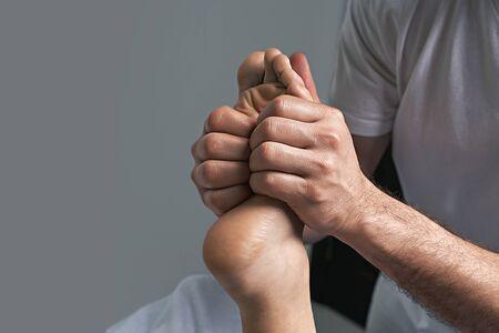 Male masseur hands doing reflexology massage on female foot reflex zones in the spa salon.