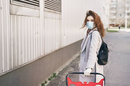 Young woman wearing protection face mask against coronavirus COVID-2019, novel coronavirus 2019-nCoV pushing a shopping cart on supermarket department store wall background. Concept of coronavirus quarantine and pandemic. Imagens