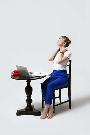 Tired young female student sitting at desk working or studying remotely online massages her neck to relieve stress. Distant learning or remote work from home. Isolated on white background.