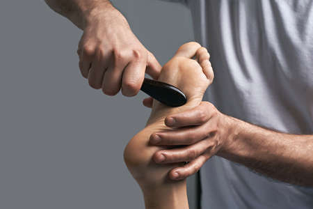 Male masseur hands doing massage on female foot reflex zone in the spa salon using gua sha scraping acupuncture tool.