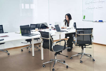 Thoughtful confident caucasian business woman or manager alone in modern office. Lady is sitting at table in meeting room of a software development company or technology startup.