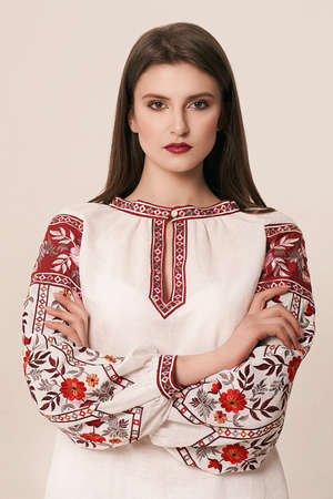 Young beautiful brunette girl wearing gorgeous ethnic style embroidered shirt, modern derivative from traditional Ukrainian vyshyvanka design. Fashion model in studio.