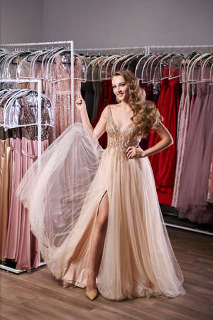 Beautiful blonde girl wearing a full-length yellow Champaign chiffon slit prom ball gown decorated with golden sequins. Model in dress hire service with many dresses in different color and style.