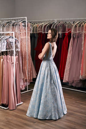 Young beautiful brunette girl wearing a full-length draped sky blue satin slit prom ball gown decorated with embroidered roses pattern. Dress hire service with many dresses on background.