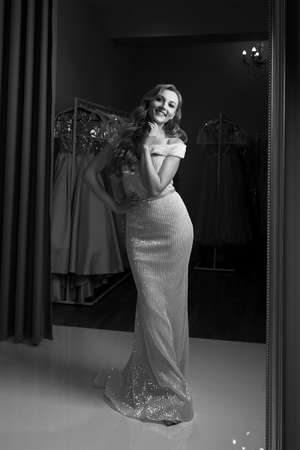 Young beautiful blonde girl wearing a full-length chiffon mermaid dress or prom ball gown decorated with sequins. Model in front of mirror in a fitting room. Black and white classic style.