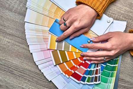 Color wheel for choosing paint tone. Hands of female interior designer working with palette for choosing colors. Creative process concept. Comparing options with matching hues. 写真素材