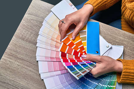 Color wheel for choosing paint tone. Hands of female interior designer working with palette for choosing colors. Creative process concept. Comparing options with matching hues.
