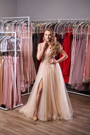Beautiful blonde girl wearing a full-length yellow champaign chiffon slit prom ball gown decorated with golden sequins. Model in dress hire service with many dresses in different color and style. 免版税图像