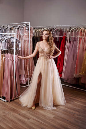 Young beautiful blonde girl wearing a full-length beige yellow champaign chiffon slit prom ball gown decorated with golden sparkles and sequins. Fashion model in dress hire service with many dresses.