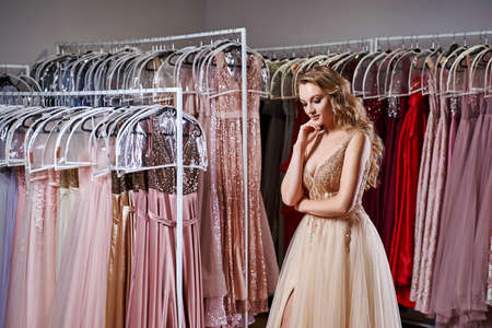 Young beautiful blonde girl wearing a full-length beige yellow champaign chiffon slit prom ball gown decorated with golden sparkles and sequins. Fashion model in dress hire service with many dresses. 免版税图像 - 162446476