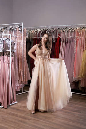 Young beautiful brunette girl wearing a full-length beige yellow champaign chiffon slit prom ball gown decorated with golden sparkles and sequins. Dress hire service with many dresses on background.