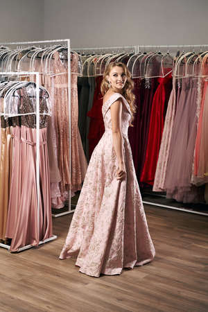 Young beautiful blonde girl wearing a full-length draped one shoulder pale pink satin slit prom ball gown decorated with embroindered pattern. Dress rental service with many dresses in on background.