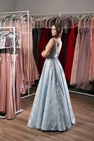 Young beautiful brunette girl wearing a full-length draped sky blue satin slit prom ball gown decorated with embroindered roses pattern. Dress hire service with many dresses on background. 免版税图像