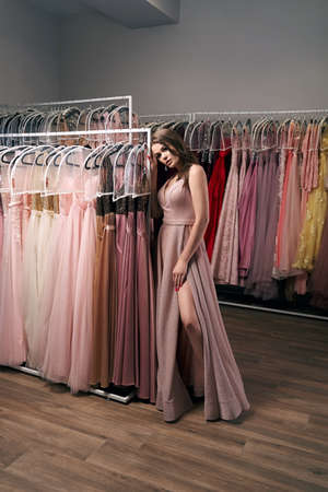 Portrait of young beautiful girl wearing a full-length pale pink glitter chiffon draped prom ball gown. Model selecting an outfit for occasion in dress hire service with many options on background.