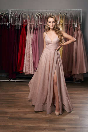 Young beautiful blonde girl wearing a full-length pale pink glitter chiffon draped prom ball gown. Model selecting an outfit for occasion in dress hire service with many options on background. 免版税图像