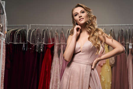 Young beautiful blonde girl wearing a full-length pale pink glitter chiffon draped prom ball gown. Model selecting an outfit for occasion in dress hire service with many options on background. 免版税图像 - 162446445