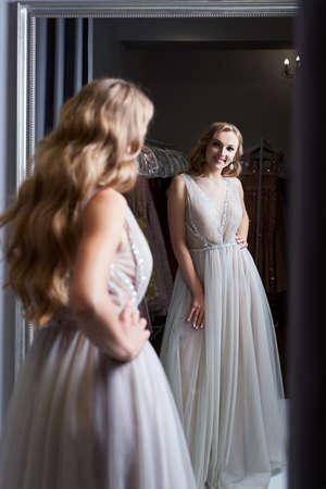 Young beautiful blonde girl wearing a full-length silver white chiffon prom ball gown decorated with sparkles and sequins. Model in front of mirror in a fitting room at dress hire service. 免版税图像