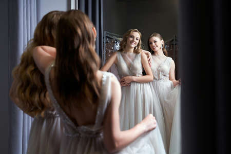 Two young beautiful girls wearing a full-length silver white chiffon prom ball gowns decorated with sparkles and sequins. Models in front of mirror in a fitting room. 免版税图像 - 162446413