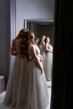 Two young beautiful girls wearing a full-length silver white chiffon prom ball gowns decorated with sparkles and sequins. Models in front of mirror in a fitting room.