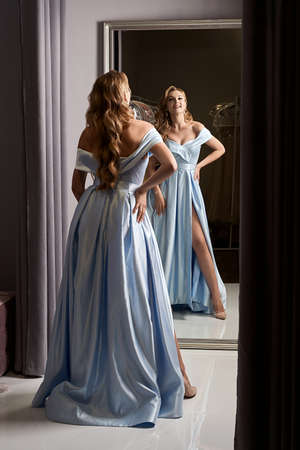Young beautiful blonde girl wearing an off-the-shoulder full-length sky blue satin slit prom ball gown. Model looking in mirror. Fitting room in dress hire service.
