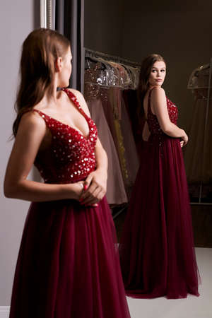 Young beautiful brunette girl wearing a full-length dark crimson red chiffon prom ball gown decorated with sparkles and sequins. Model in front of mirror in a fitting room at dress hire service. Standard-Bild
