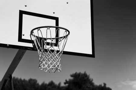 Outdoor basketball hoop or goal on sky background in black and white. 免版税图像