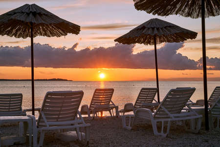 Straw beach umbrellas and chairs on a sunset beach with beautiful clouds