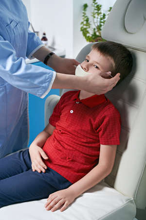 Female doctor taking off or putting on a protective face mask from a boy patent before medical examination