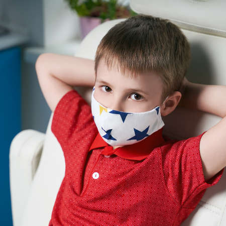 Little boy patient wearing a protective face mask sitting in a medical examination chair