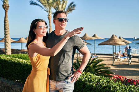 Beautiful caucasian couple on sea vacation in a tropical resort. Woman is pointing at something interesting on the horizon.