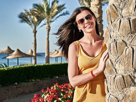 Beautiful caucasian lady with dark hair in yellow dress stands by a palm tree at luxury tropical resort 免版税图像