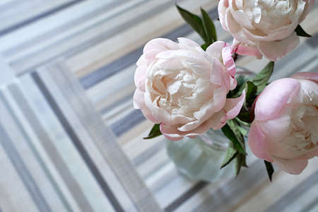 A bouquet of peonies in a transparent glass vase. Pink and white peonies on the table covered with pattern serving mats