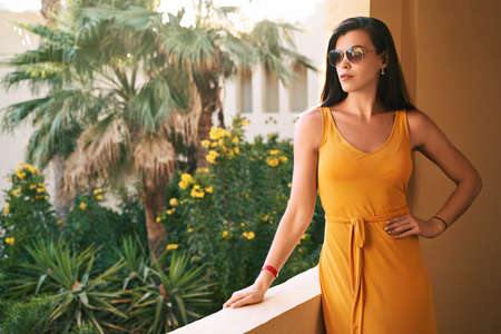 Beautiful caucasian lady in yellow dress and sunglasses stands in a shady arcade or balcony at luxury tropical resort hotel with palms and flowers on background
