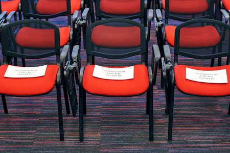 Red and black conference chairs in the auditorium with reservation for the speakers sign on them 免版税图像