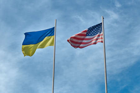 Flags of Ukraine and USA - United States of America waving in the wind at poles on cloudy sky background