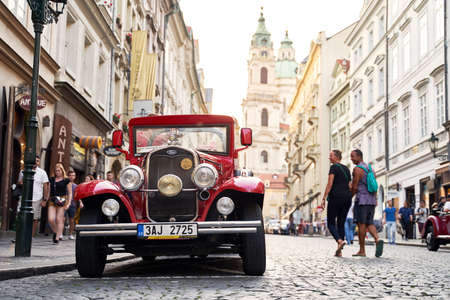 Vintage red Ford Model A car used for tourist attraction parked on the Mostecka street in historical Mala Strana district.